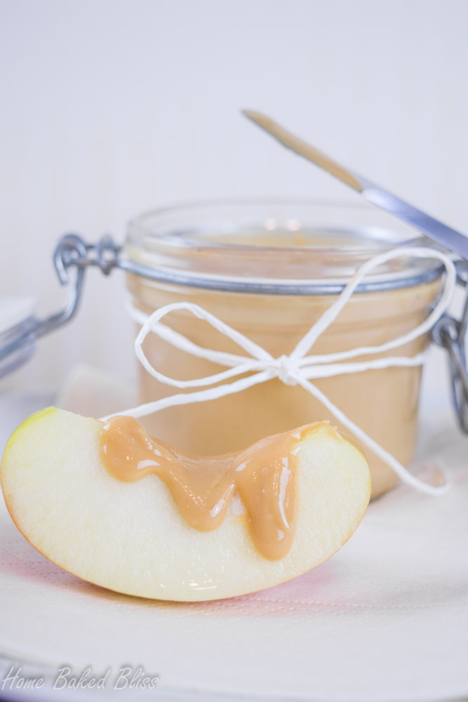 A jar of homemade peanut butter next to an apple slice drizzled with peanut butter.