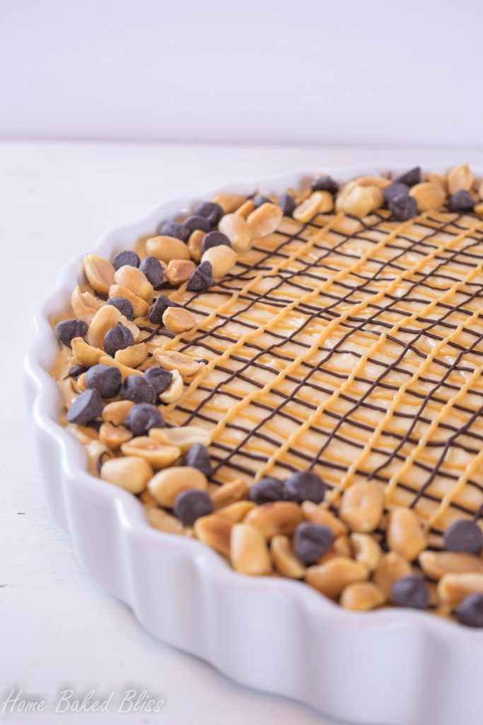 Peanut butter chocolate pie drizzled with chocolate and peanut butter and decorated with chocolate chips and peanuts.