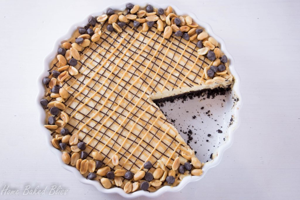 Chocolate peanut butter pie in a white pie pan with a slice cut out.