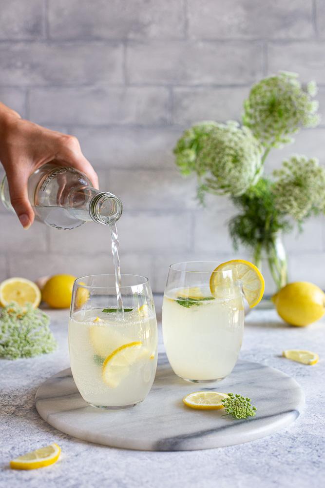 Pouring homemade lemonade into glasses
