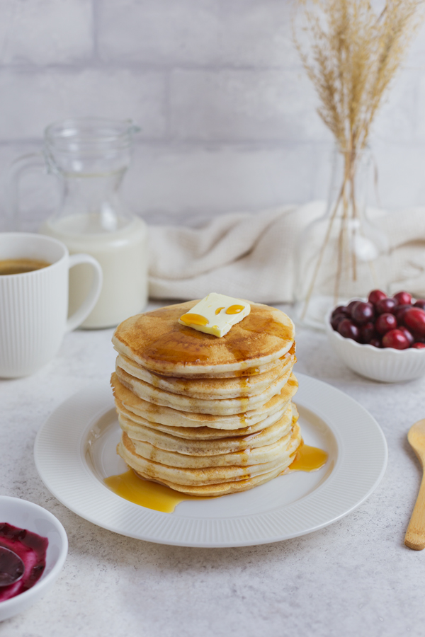 A stack of vegan pancakes garnished with vegan butter