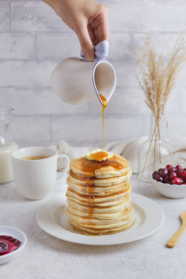 Pouring maple syrup over vegan pancake stack