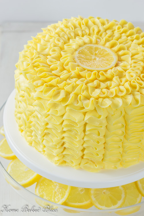 Lemon Ruffle Cake filled with lemon curd on a white cake stand.