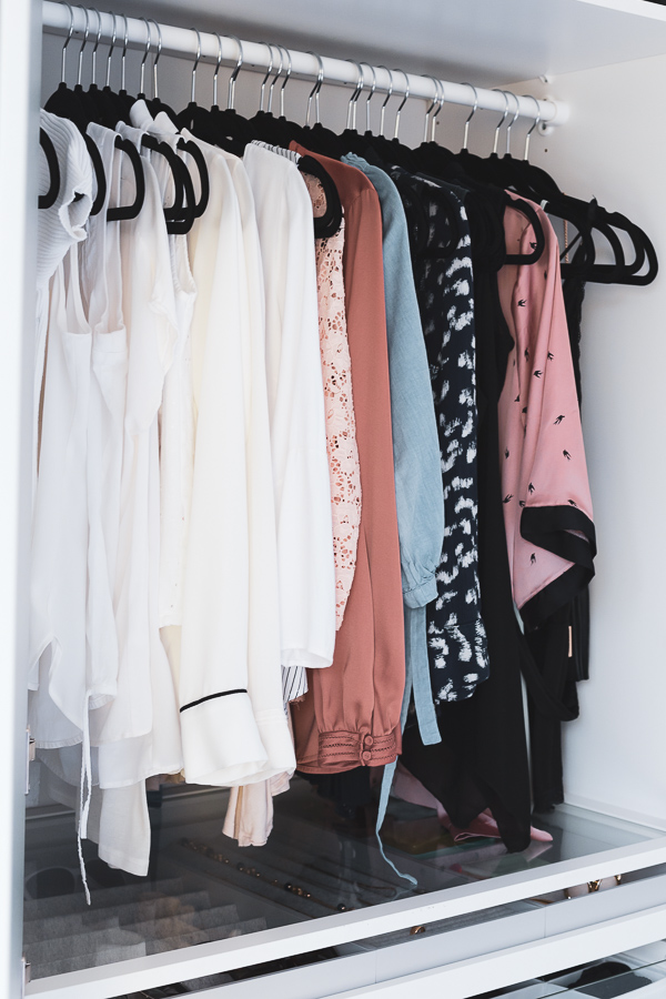 Clothes hung up and ordered by color