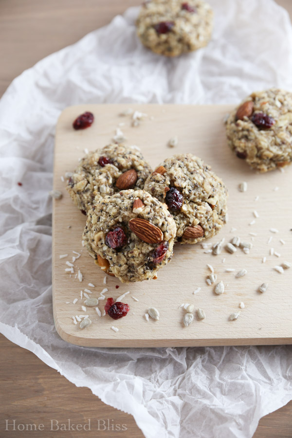 Three breakfast cookies with cranberries and coconut on a wooden board.
