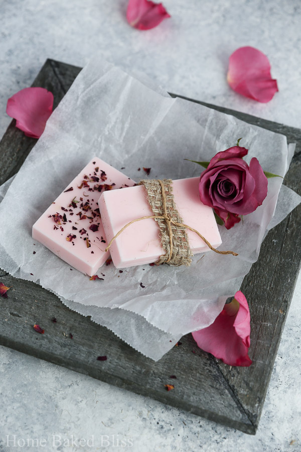 Two bars of diy rose soap on a wooden plate decorated with twine and rose petals.