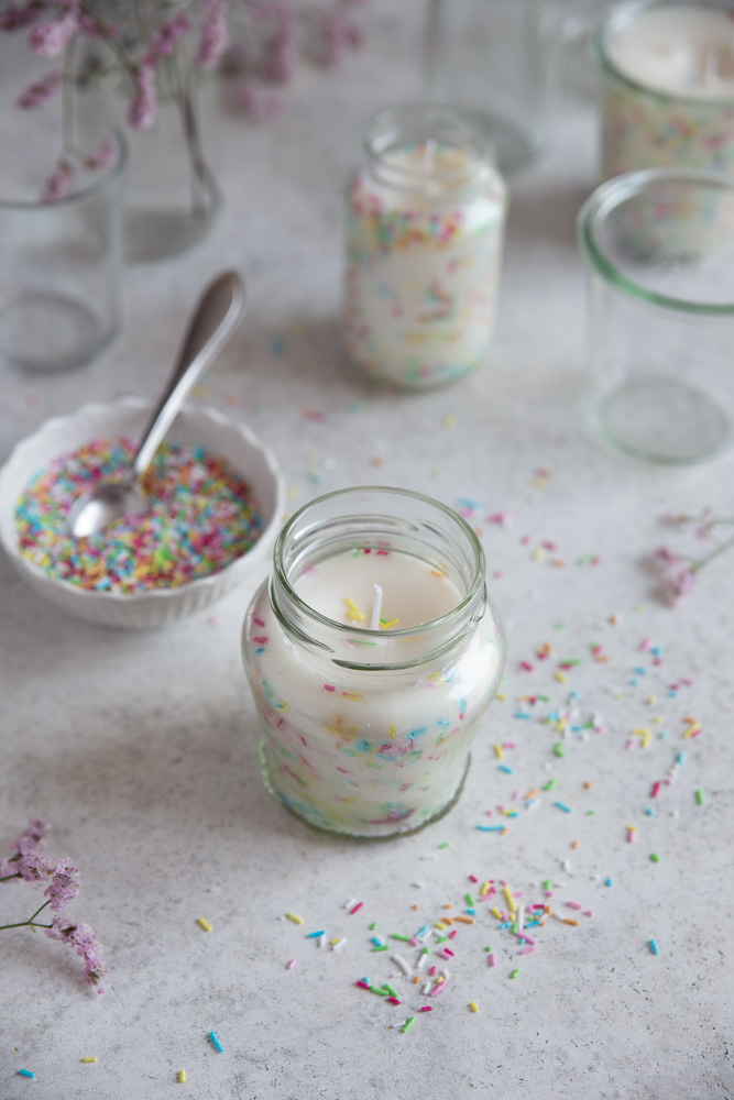 A DIY sprinkle candle next to a bowl of sprinkles