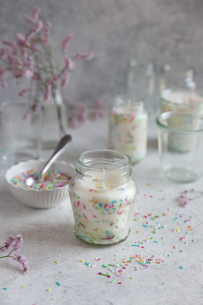 Three funfetti candles on a white surface