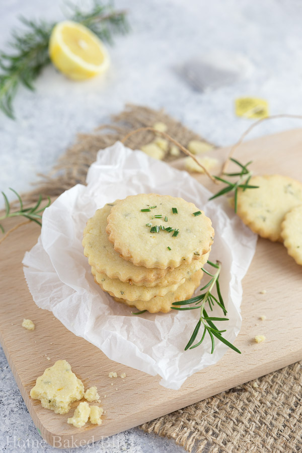 Rosemary lemon cookies stacked in a pile, sprinkled with fresh rosemary sitting on a cutting board