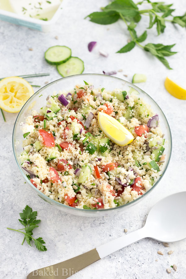 A colourful couscous salad with cucumber, tomatoes, feta cheese and onions in a glass bowl.