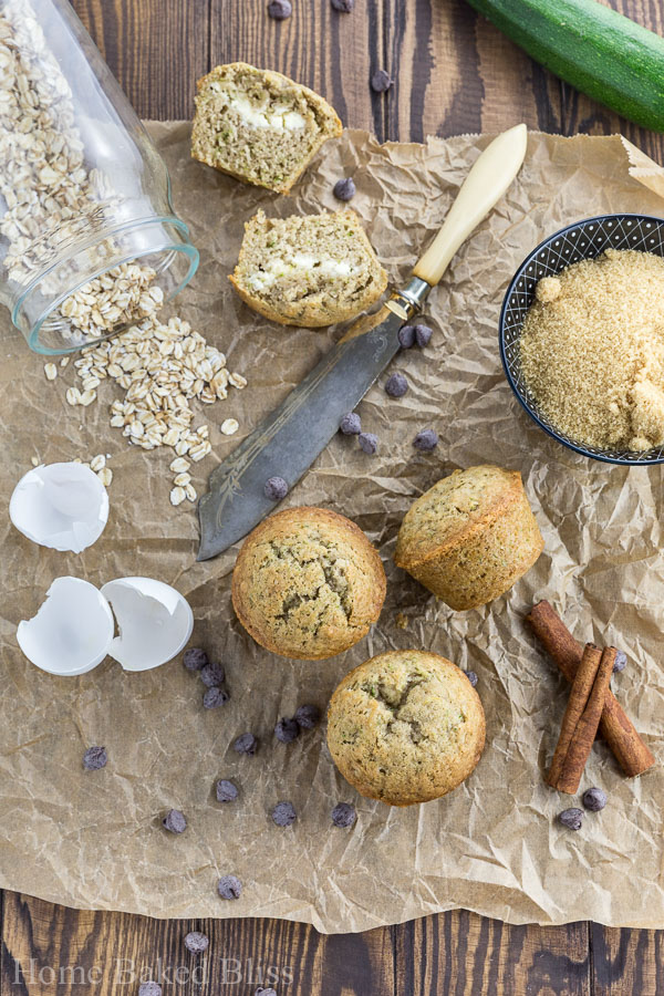 Zucchini muffins filled with cream cheese next to oats and egg shells.