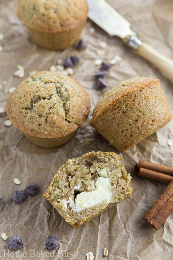 A closeup of the zucchini muffins filled with cream cheese on brown parchment paper.