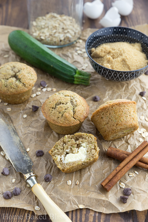 Zucchini muffins filled with cream cheese next to a butter knife and cinnamon sticks.