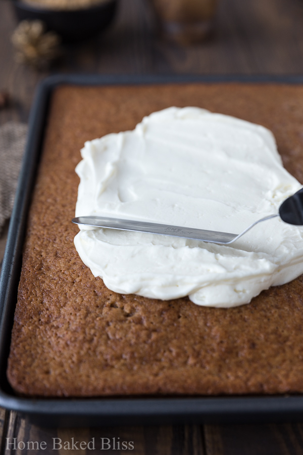 Frosting being spread onto a spice sheet cake with a spatula
