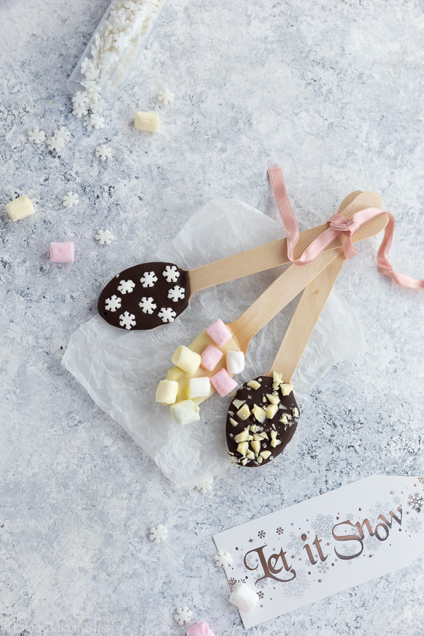 Chocolate spoons garnished with snowflake sprinkles, marshmallows and chocolate sprinkles.
