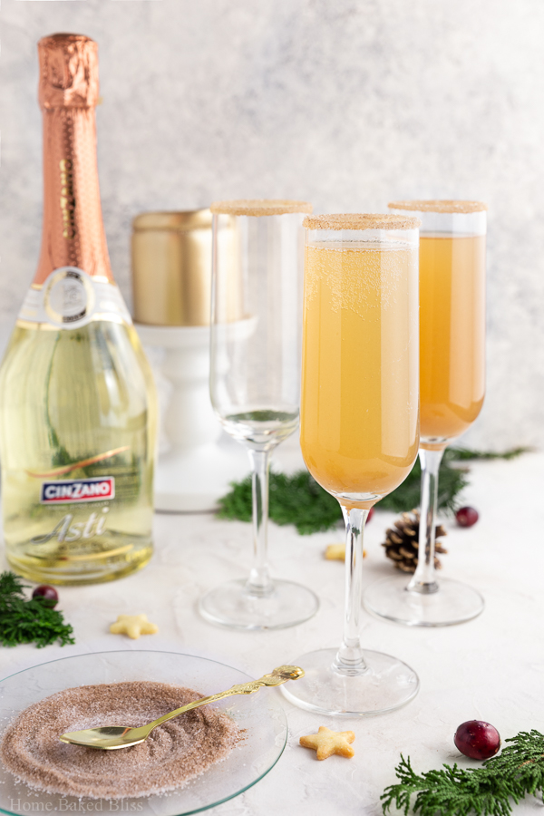 Two glasses of apple cider mimosas in Champagne glasses next to a bottle of Prosecco