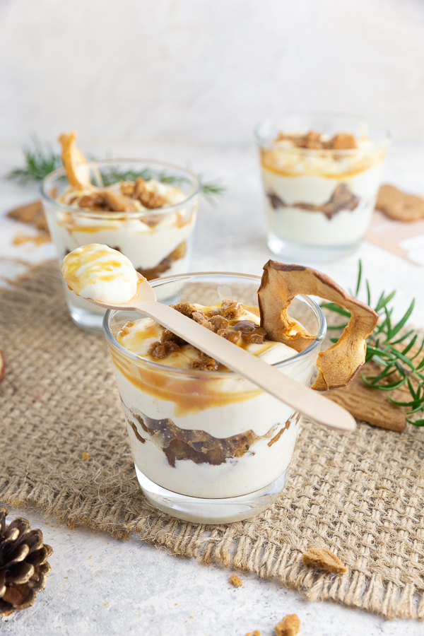 Speculoos tiramisu with cinnamon apples and caramel sauce in glasses with a wooden spoon on top.