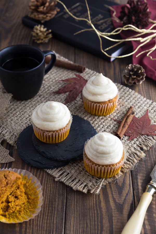 Three pumpkin cupcakes with cinnamon frosting on a piece of burlap.