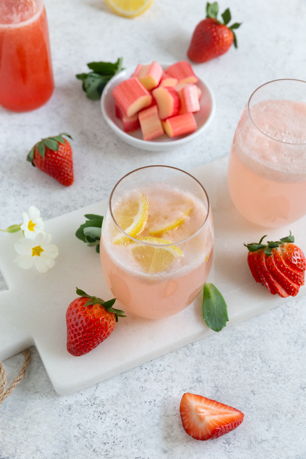 A glass of strawberry rhubarb lemonade garnished with fresh lemons