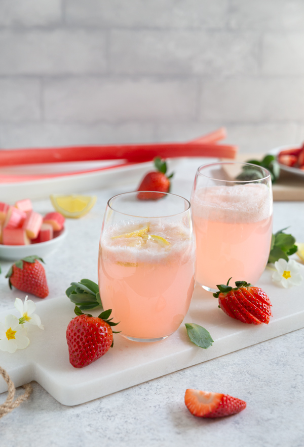 Two glasses of strawberry rhubarb lemonade on a white serving tray