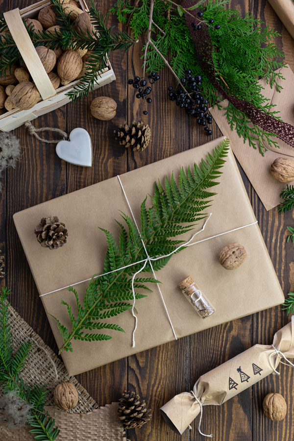 A large gift wrapped in brown paper decorated with a fern leaf