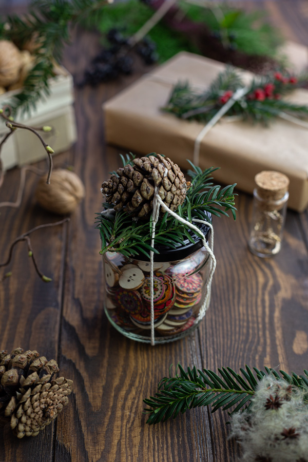 Buttons in a glass jar decorated with a pine cone and greenery