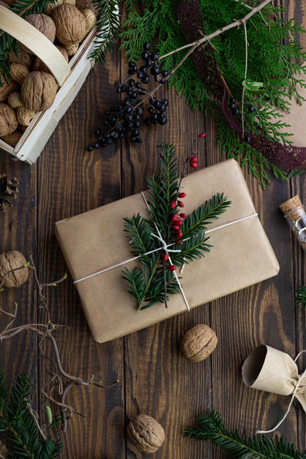 A small present wrapped in brown paper and decorated with holly