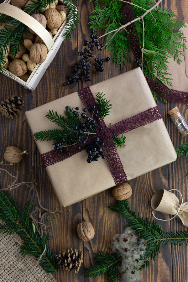 A large gift wrapped in brown paper and decorated with blue holly