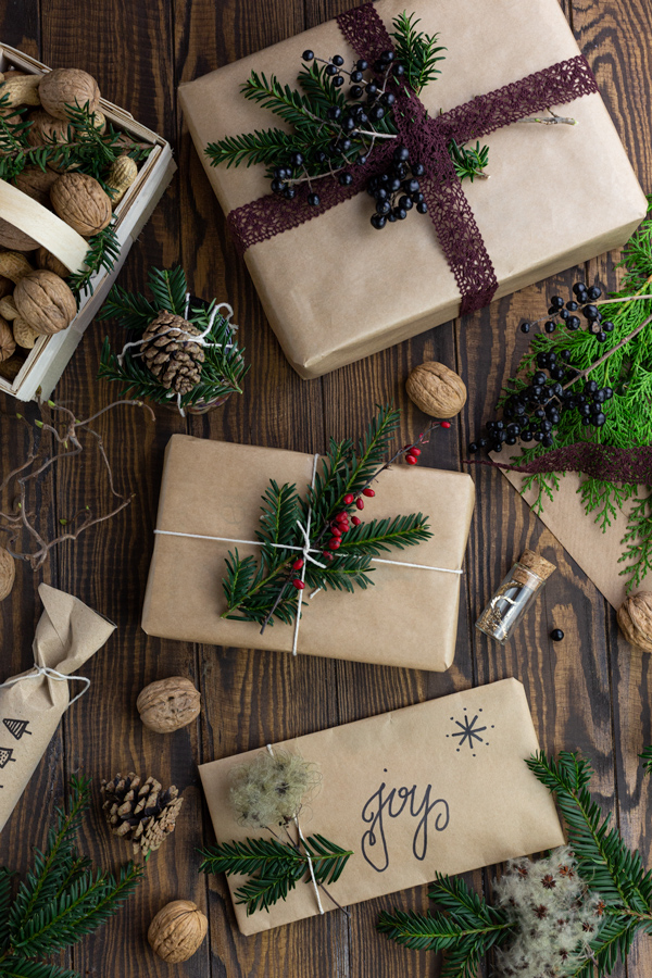 Various gifts wrapped in brown paper and decorated with greenery