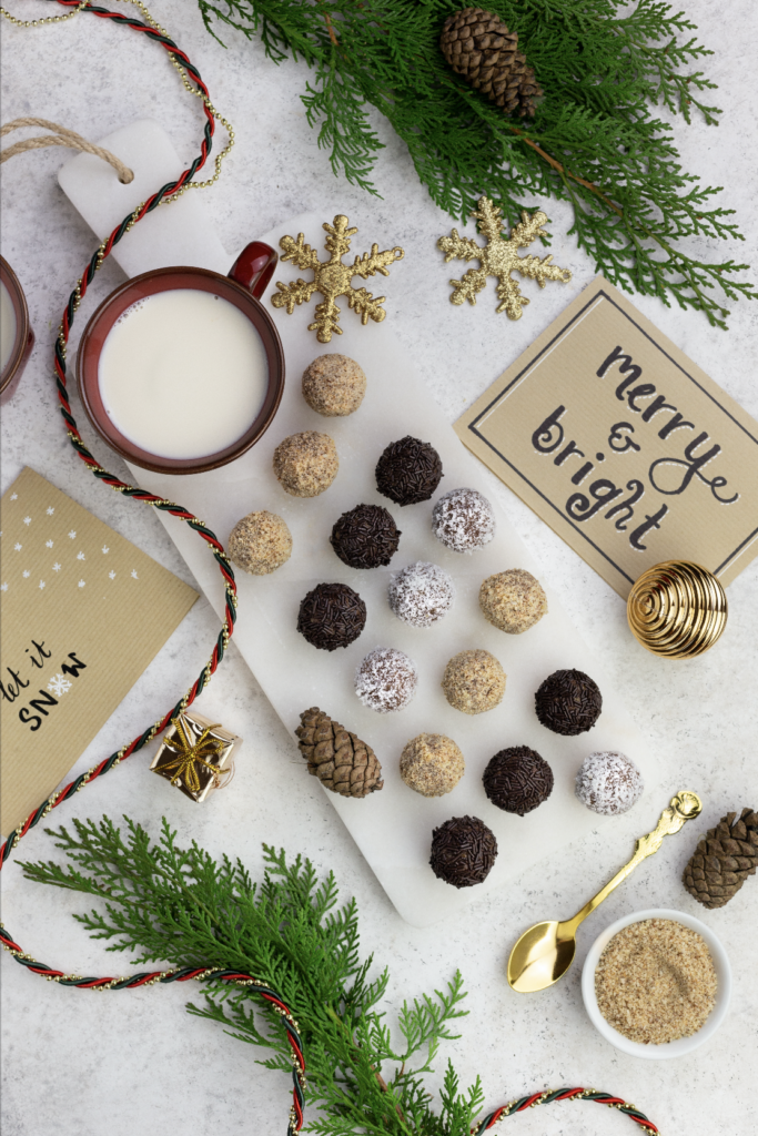 Vegan rum truffles on white plate next to a cup of milk and Christmas cards