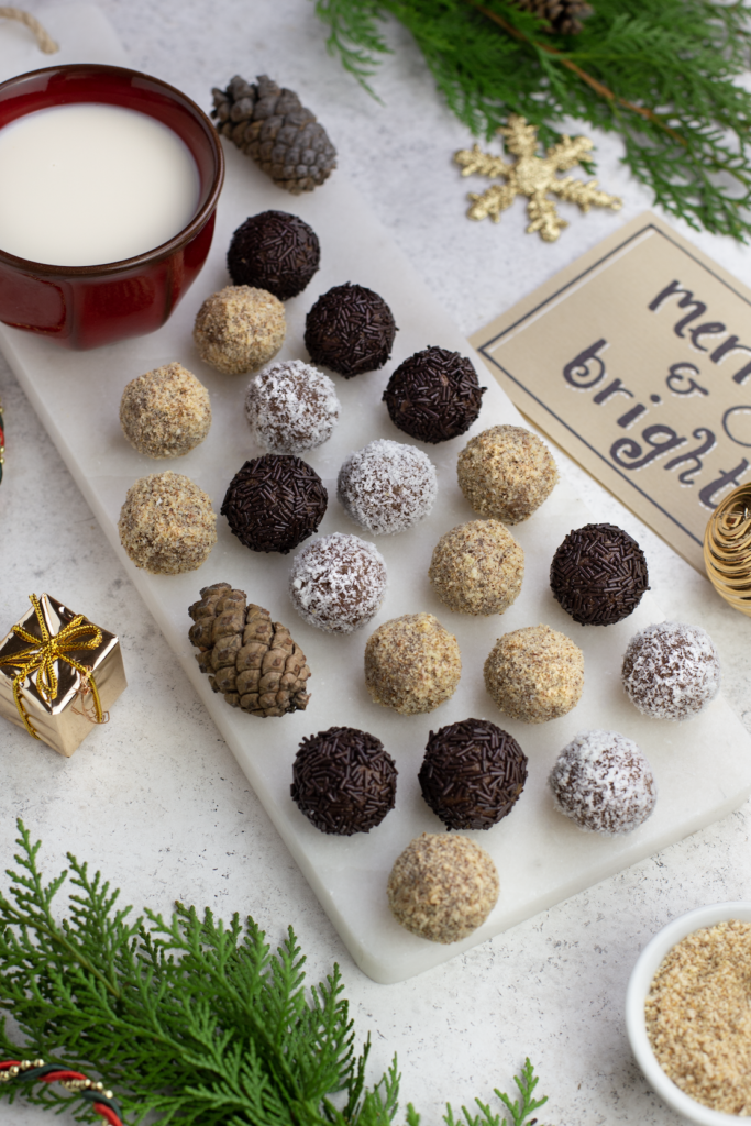 An assortment of vegan rum truffles coated in coconut, hazelnut and chocolate sprinkles on white plate