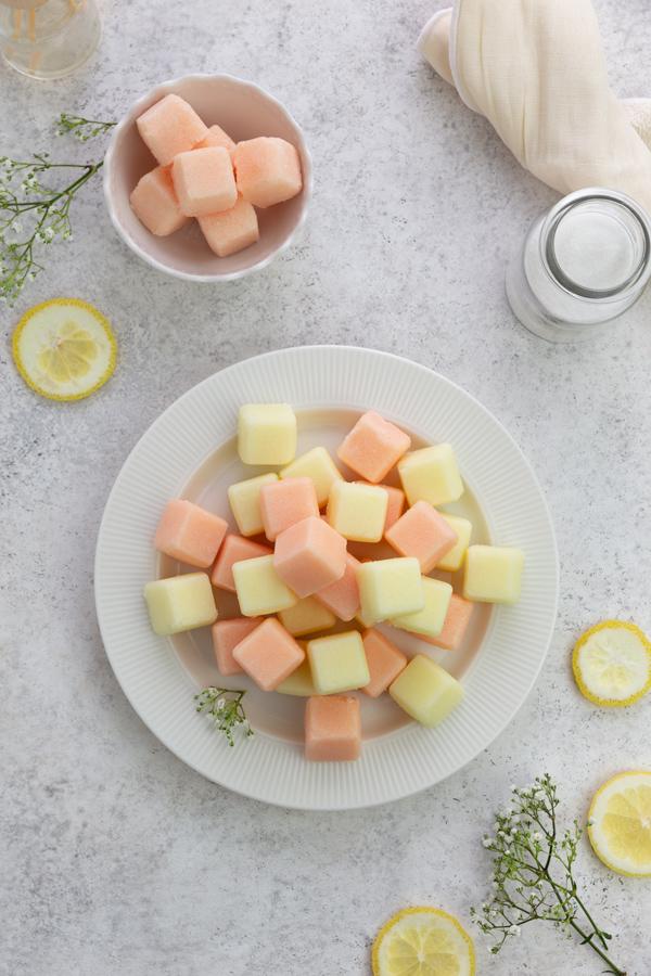 Pastel Zuckerpeeling-Würfel mit Zitrus Düften auf weissen Hintergrund