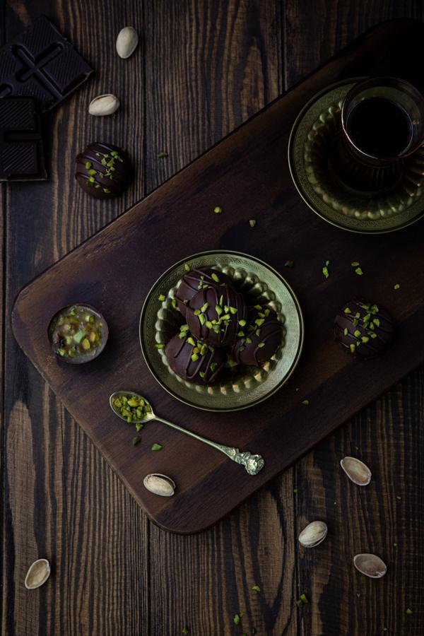 Miso-Karamell-Trüffel mit Pistazien neben einer Tasse Kaffee