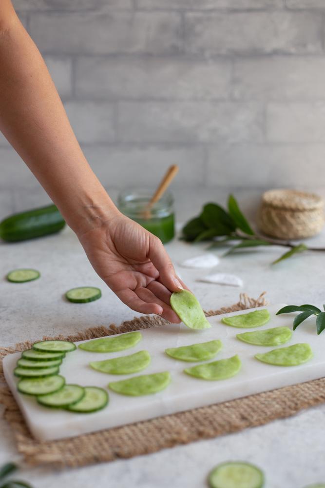 Laying cucumber eye pads onto a white tray