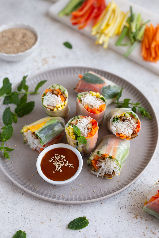 Vegan rice paper rolls next to a bowl with peanut dipping sauce