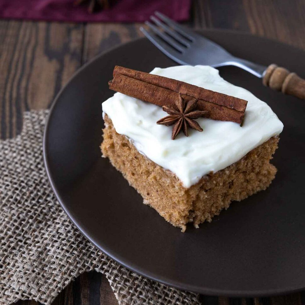A slice of the spice sheet cake garnished with star anis and a cinnamon stick