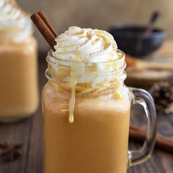 A pumpkin spice latte in a mason jar garnished with whipped cream and a cinnamon stick.
